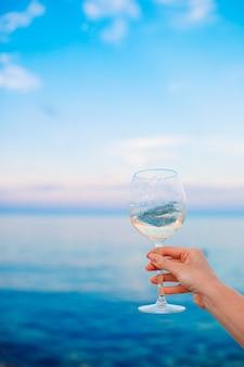 Taça de vinho branco na praia tropical ao pôr do sol