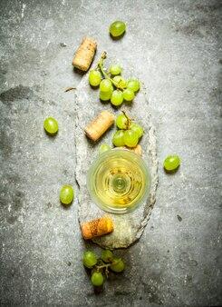Taça de vinho com tubos e uvas brancas
