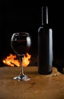 Taça de vinho e garrafa de vinho na superfície de madeira rústica com fogo atrás