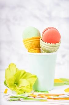 Taça de wafer para sorvete com macarons e gladíolo verde sobre fundo claro de mármore, copie o espaço