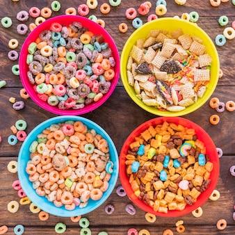 Taças brilhantes com cereais na mesa de madeira