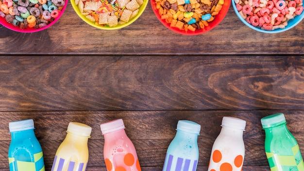 Taças brilhantes de cereais com garrafas de leite