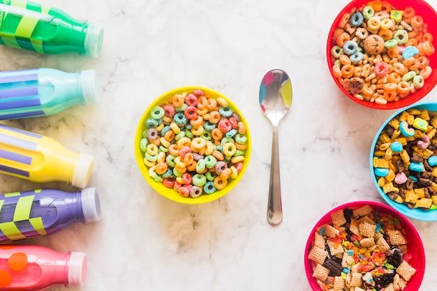 Taças com cereais e garrafas de leite na mesa
