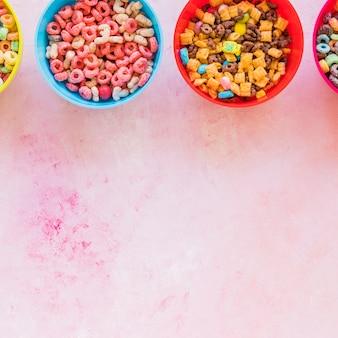 Taças com cereais na mesa-de-rosa
