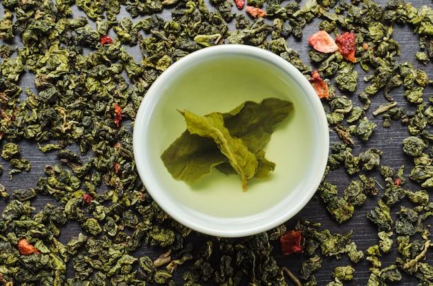 Taças com chá verde folha de oolong e morangos