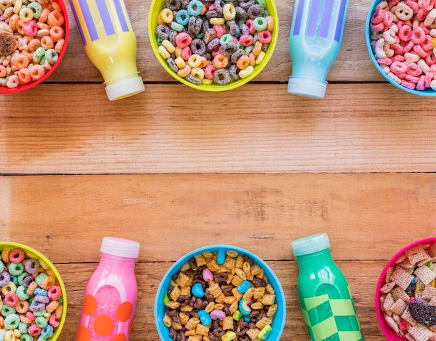 Taças com diferentes cereais e garrafas de leite