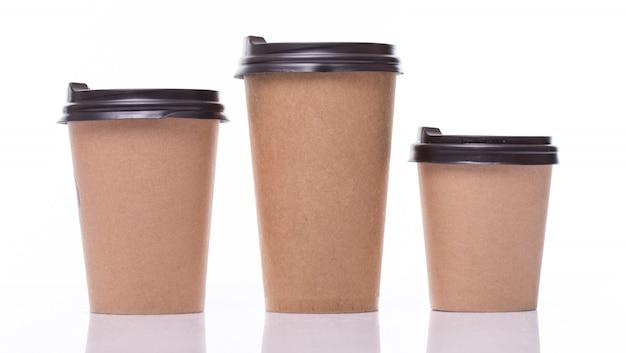Taças de café de papel coberto tamanhos diferentes isolados no branco