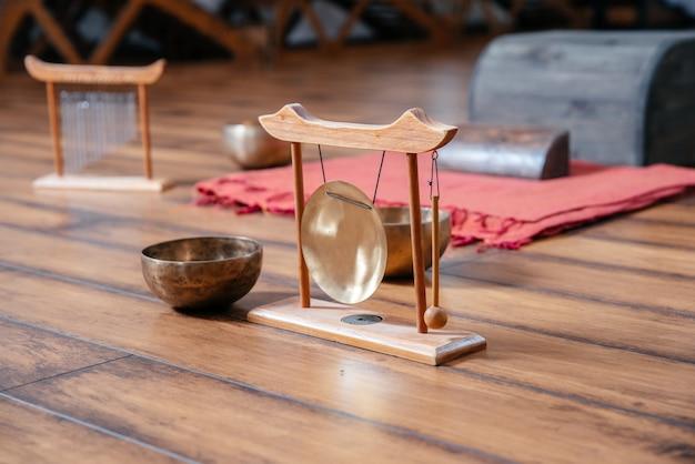 Taças de canto tibetano no chão em aula de ioga, conceito de terapia de som