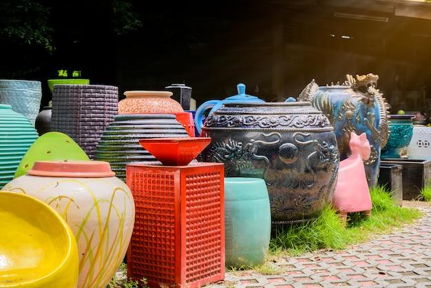 Taças de cerâmica multicoloridas, potes coloridos e copos ou vasos artesanais.