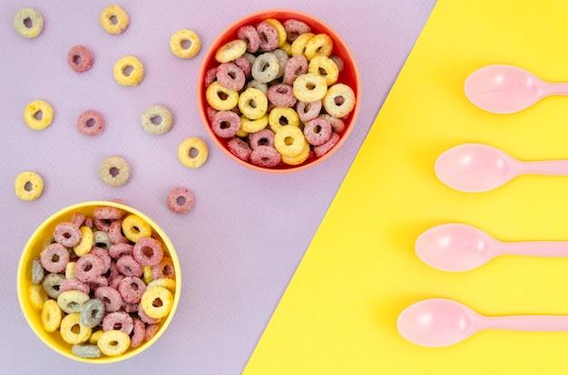 Taças de cereais e colheres amarelas e vermelhas