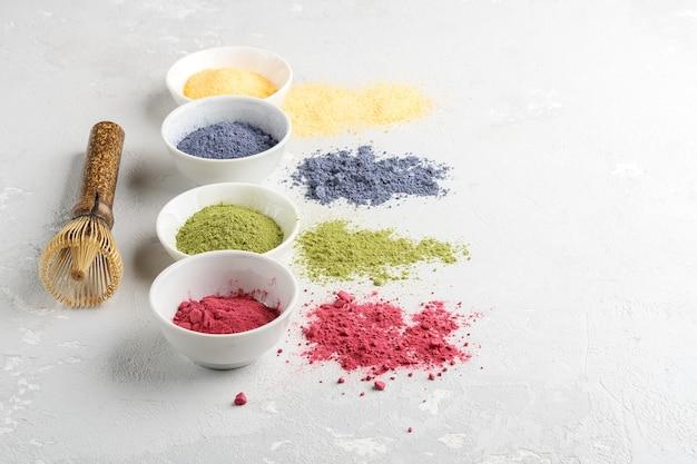 Taças de chá matcha multicolorido em pó.