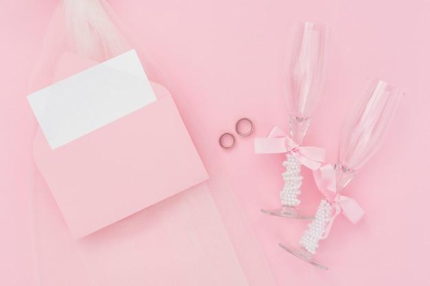 Taças de champanhe ao lado de convite de casamento