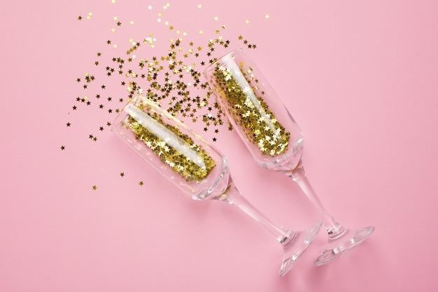 Taças de champanhe com confete de estrelas douradas em papel rosa