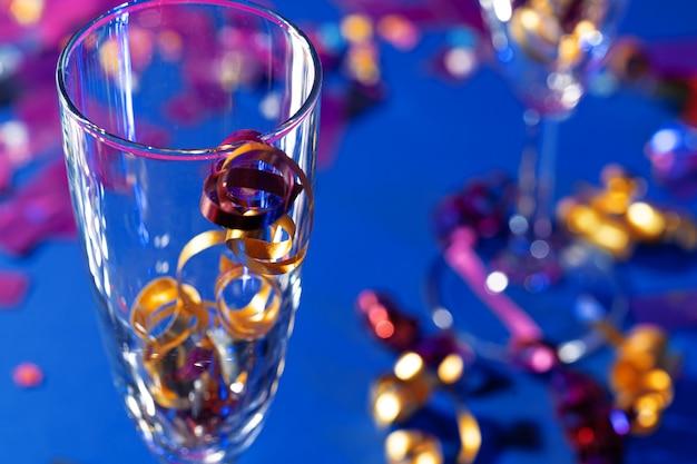 Taças de champanhe com enfeites de festa no fundo brilhante
