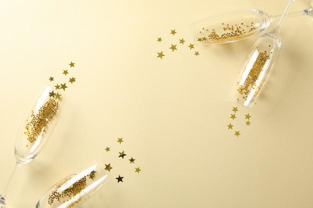 Taças de champanhe com glitter em bege, espaço para texto