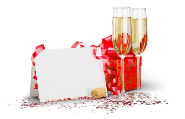 Taças de champanhe com serpentina, cartão em branco e caixa de presente
