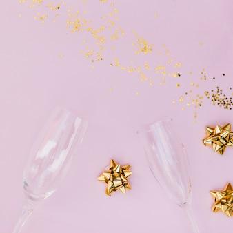 Taças de champanhe; confete e arco no pano de fundo rosa