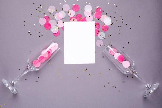 Taças de champanhe e cartão com confete rosa