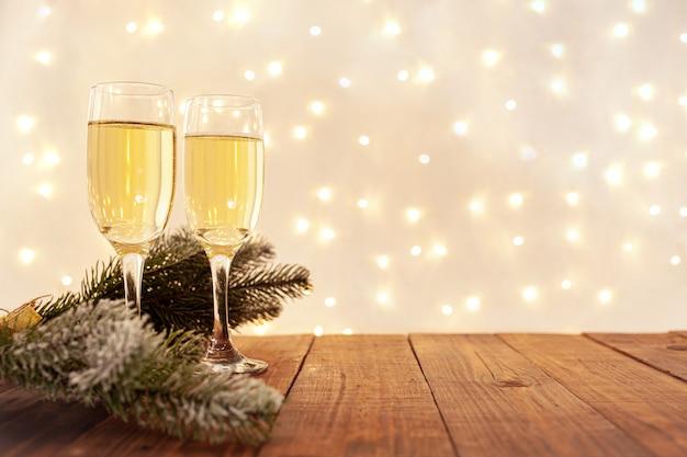 Taças de champanhe em uma mesa de madeira com uma guirlanda dourada borrada, conceito de véspera de ano novo