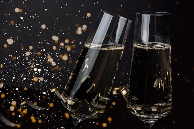 Taças de champanhe em uma parede escura com neve e luzes. véspera de ano novo, natal
