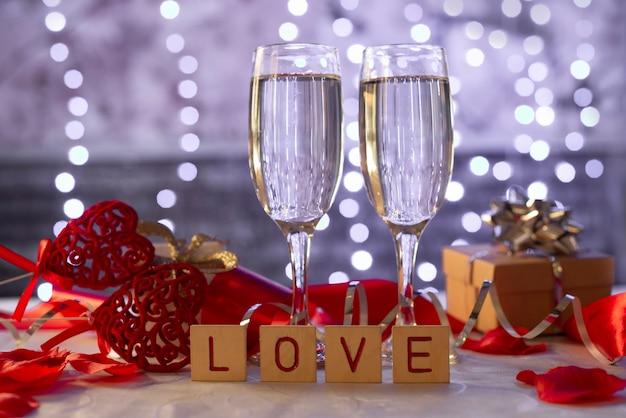 Taças de champanhe, love em blocos de madeira, corações e uma caixa de presente para a festa do dia dos namorados em fevereiro