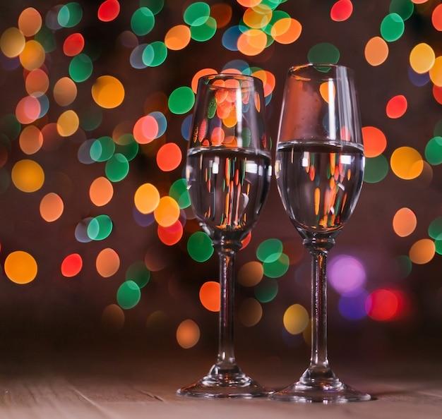 Taças de champanhe no fundo das luzes de natal.