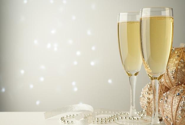 Taças de champanhe perto de bolas de natal e fitas branco-prateadas