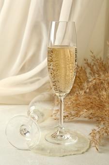 Taças de champanhe, resina epóxi e flores do campo na mesa branca Foto Premium