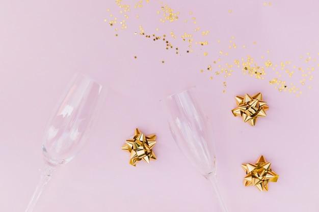 Taças de champanhe transparentes; arco dourado e confetes em fundo rosa