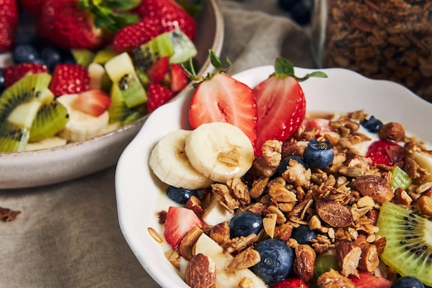 Taças de granola com iogurte, frutas e morangos em uma superfície branca