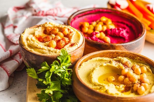 Taças de homus diferentes. hummus de grão de bico, hummus de abacate e hummus de beterraba.