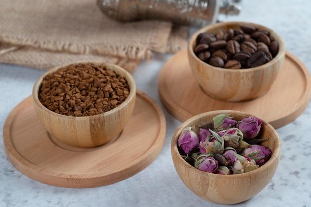 Taças de madeira cheias de grãos de café aromáticos, café e flores secas de rosas.