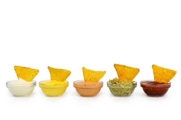 Taças de molho mexicano com tortilhas, guacamole, chili, cru, colorau.