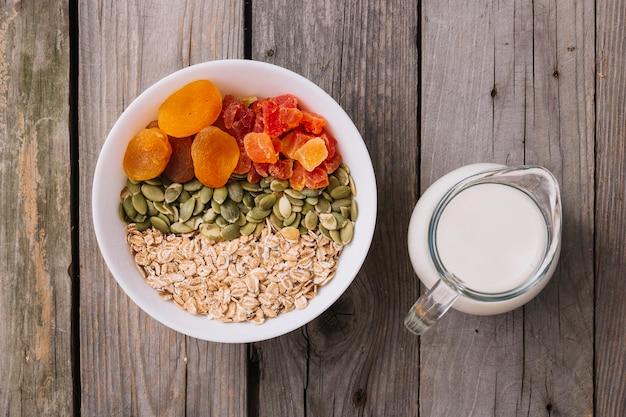 Taças de muesli, sementes de abóbora e frutas secas na tigela com jarro de leite na mesa de madeira rústica