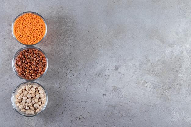 Taças de vidro cheias de lentilha crua, ervilhas e feijão em fundo de pedra.