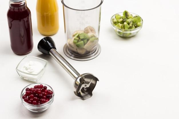 Taças de vidro com cranberries e kiwi. liquidificador e jarro liquidificador com banana. ingredientes para fazer smoothies de frutas. vista do topo. copie o espaço