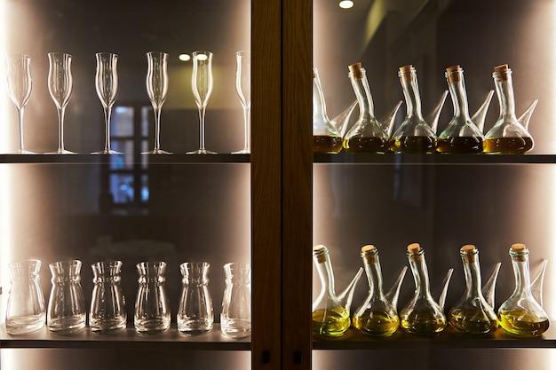 Taças de vidro e garrafas em armário de madeira