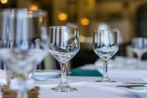Taças de vidro sobre uma mesa com toalha de mesa branca e talheres em cima da mesa.