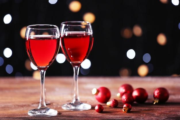 Taças de vinho com enfeites de natal na mesa de madeira