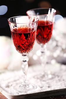 Taças de vinho com enfeites de natal na mesa de neve, close-up