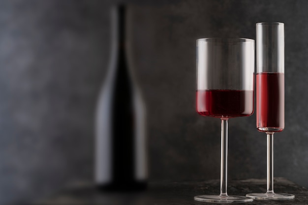 Taças de vinho e uma garrafa de vinho tinto em um fundo cinza embaçado,