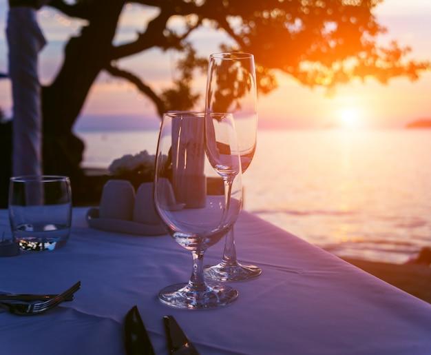 Taças de vinho na mesa do bar. pôr do sol sobre o mar