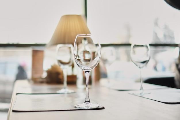 Taças de vinho na mesa. muitos copos prontos para servir bebidas em uma festa. jantar de negócios.