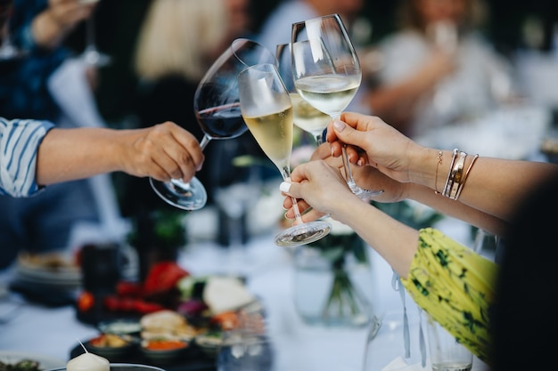 Taças de vinho nas mãos de pessoas na festa. foto de alta qualidade