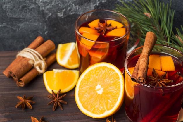 Taças de vinho quente com galhos de árvore do abeto na mesa de madeira