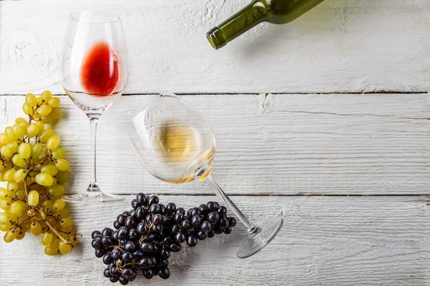 Taças de vinho, uvas pretas e verdes, garrafa na mesa de madeira branca, espaço vazio para o texto