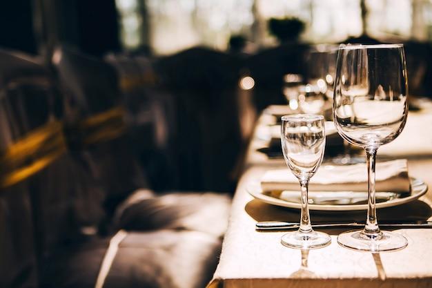 Taças de vinho vazias na luz do sol na mesa de banquete
