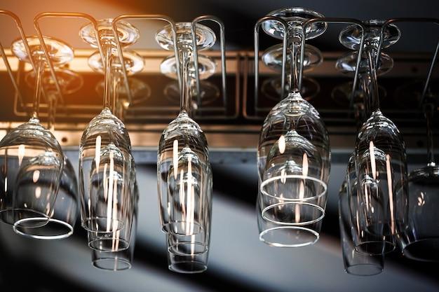 Taças de vinho vazias penduradas com o lado para baixo acima de uma prateleira de bar