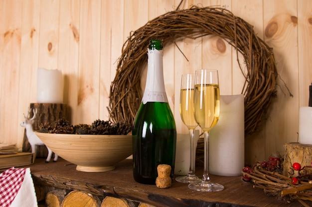 Taças e garrafas de champanhe abertas e sem rótulo sobre uma lareira de madeira rústica com uma guirlanda de natal de galho e uma tigela de pinhas em uma cabana de madeira para celebrar a época festiva