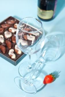 Taças vazias de champanhe ou vinho. caixa de chocolates e garrafa de vinho